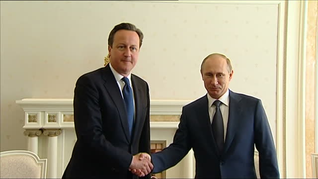Interior shots David Cameron British Prime Minister and Vladimir Putin Russian President enter room shake hands sit down David Cameron and Vladimir...