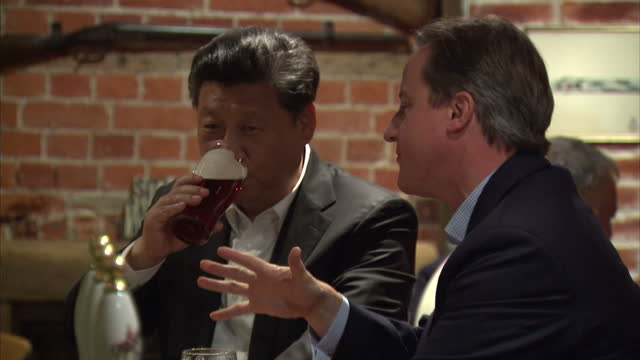 Interior shots David Cameron British Prime Minister and Xi Jinping Chinese President at The Plough pub sitting at bar talking and drinking beer on...
