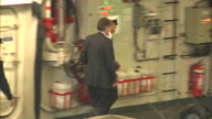 Interior shots Defence Secretary Philip Hammond follows Royal Navy officers trips up as he walks past press to assembled crew members Philip Hammond...