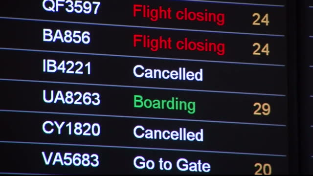 Interior shots departure boards at Heathrow airport showing cancelled flights to the New York Boston Newark Interior shot passengers sat in lounge...