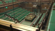 Interior shots empty HOC seats pan up and down from back benches / internal close up Crowned Portcullis emblem engraving on wall / interior shot pan...