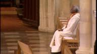 Interior shots former Archbishop in South Africa Desmond Tutu sit in prayer side of abbey at funeral of Robert Runcie former Archbishop