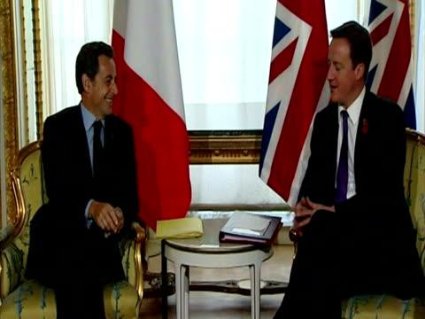 Interior shots French President Nicolas Sarkozy Prime Minister David Cameron sat chatting with diplomats delegates pose for photo call Cameron...