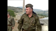 Interior shots General Ratko Mladic gets out of vehicle and greets BosnianSerb soldiers at countryside outpost on September 25 1992 in Bosnia and...