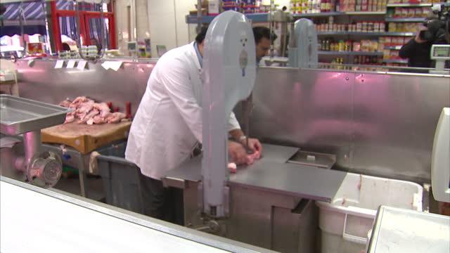 Interior shots Halal butcher slicing meat using machin Halal Butcher Using Meat Slicer on February 02 2013 in London England