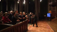 Interior shots Justin Webly clapping along to gospel singing struggling to find rhythm