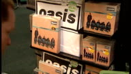 Interior shots man stocking shelves with Oasis CDs albums