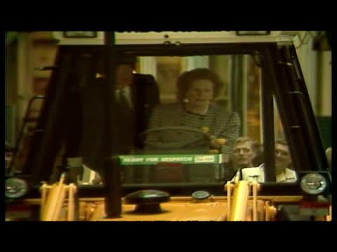 interior shots Margaret Thatcher driving JCB loader through factory also includes Dennis Thatcher