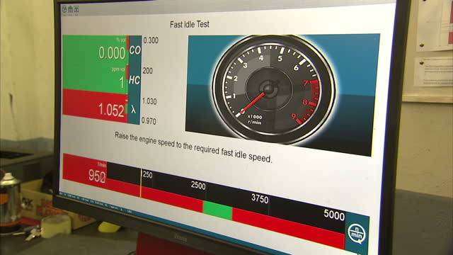 interior shots mechanic monitoring emissions testing programme on computer screen shows results and 'PASS' notification