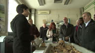 Interior shots media and officials gathered at ICMP's Podrinje Identification Project scientist speaks re forensic examination of skeletons...