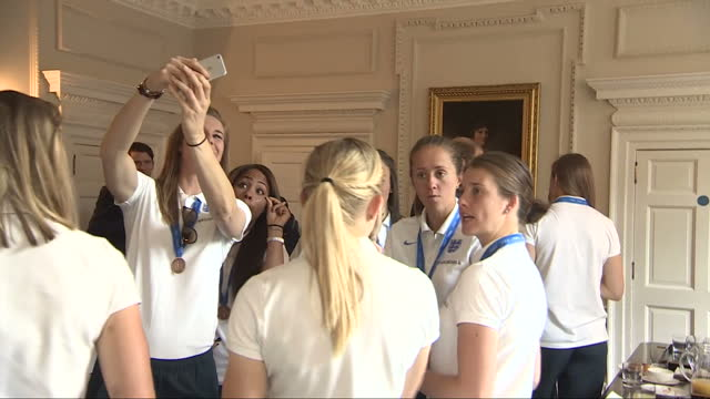 Interior shots Members of the England Woman's Football team taking photos of Prince William Duke of Cambridge as he talks with other members of the...