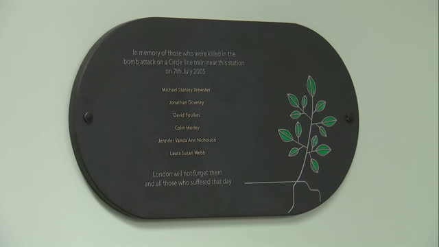 Interior shots memorial plaque on wall at Edgware Road underground station in memory of victims of 7/7 London Bombings Flowers left on floor below...