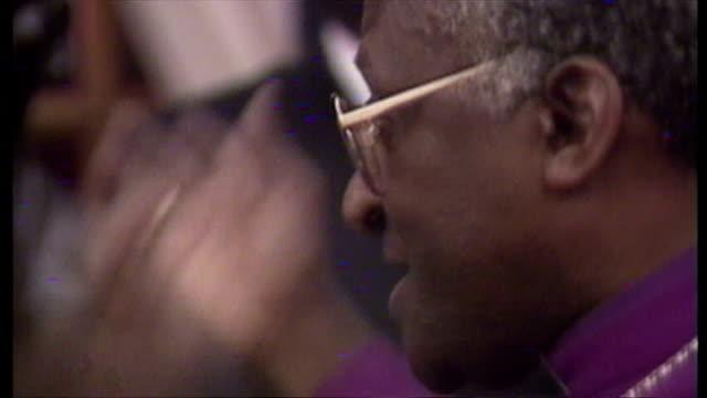 Interior shots Nelson Winnie Mandela seated listening to Archbishop Desmond Tutu speak