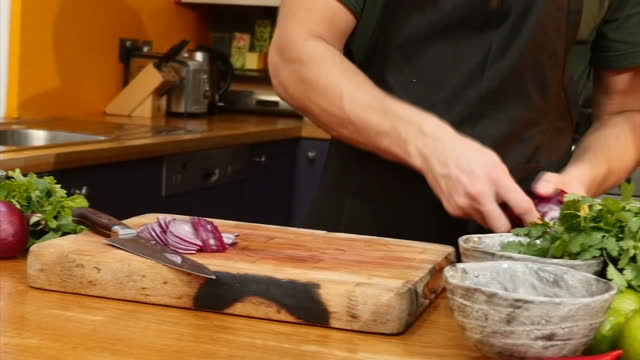 Interior shots of a chef chopping red onions preparing food in a kitchen on 14 November 2017 in London United Kingdom
