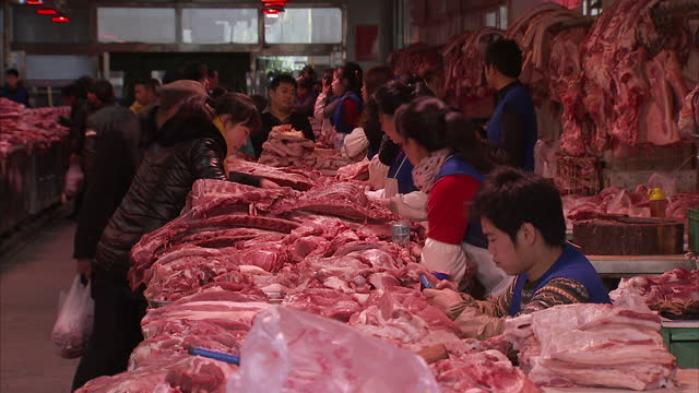 Interior shots of a covered Beijing meat market with butchers at work chopping up meat and people shopping for it on December 3 2013 in Beijing China