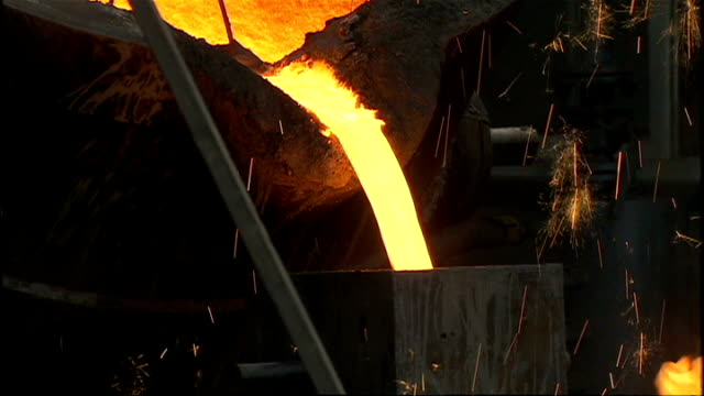Interior shots of a large steelworks with molten metal being poured by workers from huge vat into molds on July 7 2008 in Beijing China