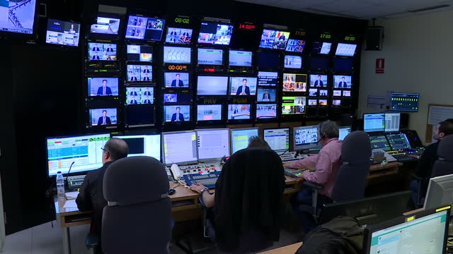 Interior shots of a TV news production gallery with vision mixer director and other staff producing the live output of Catalonia's 3/24 rolling news...