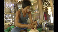 Interior shots of a villager preparing betel quid a combination of betel leaf areca nut and slaked lime and an elderley village woman smoking a large...