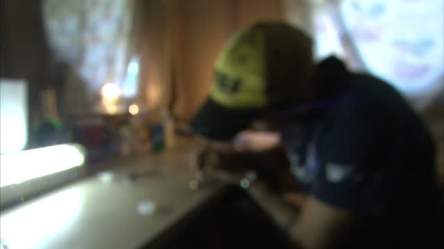 Interior shots of an anonymous male heroin user preparing a dose of heroin using a syringe and a spoon>> on July 31 2014 in UNSPECIFIED United States
