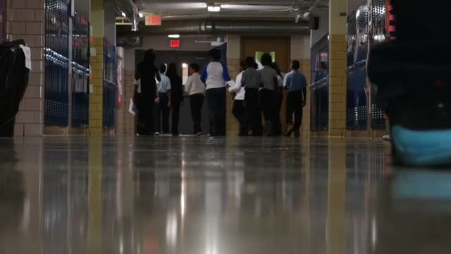 Interior shots of anonymous black elementary school pupils walking in a school corridor past lockers on January 22 2016 in Flint Michigan