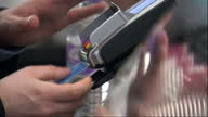 Interior shots of anonymous customers using a 'chip and pin' machine to make credit or debit card payments at a coffee shop>> on September 28 2015 in...