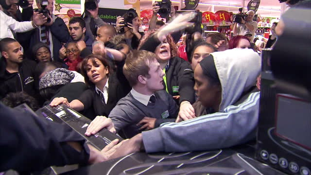 Interior shots of ASDA staff and security intervening as Black Friday bargain hunters squabble over a pile of flatscreen televisions>> on November 28...