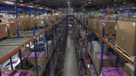 Interior shots of boxes passing along conveyor belts in a Dixons Group distribution centre and workers packing and checking boxes of goods Dixons...
