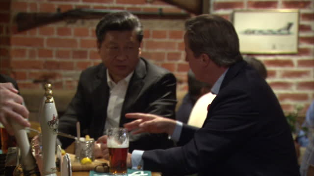 Interior shots of British Prime Minister David Cameron and Chinese President Xi Jinping in a pub near Chequers chatting drinking pints of beer and...