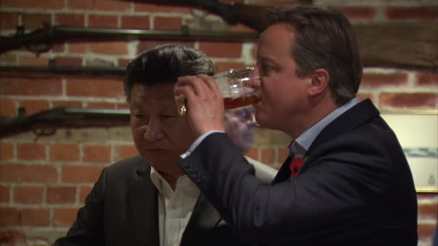 Interior shots of British Prime Minister David Cameron and Chinese President Xi Jinping drinking pints of beer in a pub near Chequers and chatting...