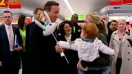 Interior shots of British Prime Minister David Cameron greeting woman with baby during visit to a Asda Supermarket David Cameron talks about raising...