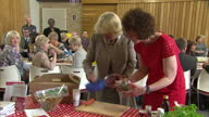 interior shots of Camilla Duchess of Cornwall grating a carrot to make a salad on her visit to the Skainos Centre on May 21 2015 in Belfast United...