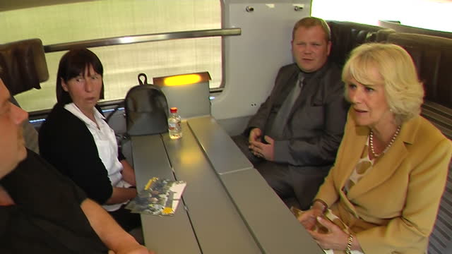 Interior shots of Camilla Duchess of Cornwall on Eurostar train taking seat and speaking with other passengers on journey Camilla Duchess of Cornwall...