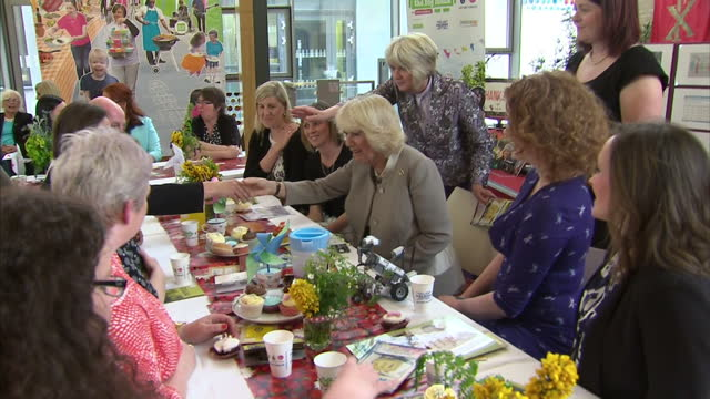 interior shots of Camilla Duchess of Cornwall pick up cupcake decorated by her and walk over to table sit down and greet women on her visit to the...
