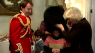 Interior shots of Camilla Duchess of Cornwall putting bearskin hat belonging to Captain Matt Wright of the Welsh Guards on little girls head at...