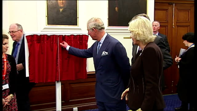 Interior shots of Camilla Duchess of Cornwall receiving teddy bear gift Prince Charles Prince of Wales opening small curtains to reveal plaque Prince...