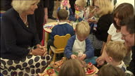 Interior shots of Camilla Duchess of Cornwall sitting down with children talking and looking at cakes made by children Camilla Duchess of Cornwall...