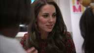 Interior shots of Catherine Duchess of Cambridge talking to people making gingerbread houses on a visit to the Heads Together Christmas party hosted...