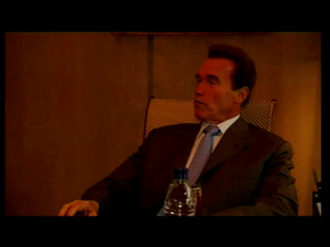 Interior shots of David Cameron and Arnold Schwarzenegger sit and talk at table under marquee
