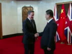 Interior shots of David Cameron meeting Chinese Prime Minister Xi Jinping shaking hands in front of flags Flag of China and Union Flag Union Jack...