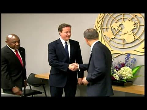 Interior shots of David Cameron Prime Minister and Ban Ki Moon UN Secretary General walk into room shake hands and pose for a photo op David Cameron...