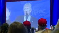 Interior shots of Donald Trump speaking at the CPAC conference with cutaways to his supporters in the audience many of whom wear 'Make America Great...