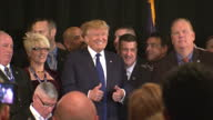 Interior shots of Donald Trump standing for photo with supporters on stage and shots of him talking to people as he makes his way out of room on...