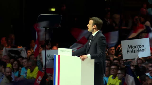 Interior shots of Emmanuel Macron on stage at a political rally as supporters cheer and wave flags on 17 April 2017 in Paris France