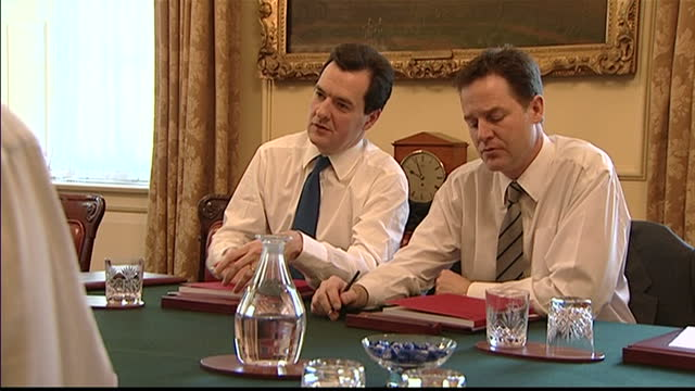 interior shots of George Osborne Chancellor of the Exchequer and Nick Clegg Deputy Prime Minister sat at table chatting with red budget reports in...