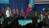 Interior shots of Hillary Clinton addressing a campaign rally in Charlotte NC with Barack Obama stood to one side with supporters holding 'Stronger...