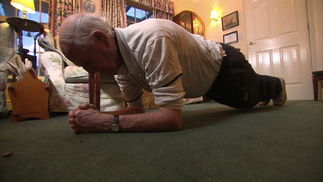 Interior shots of John Hamilton a 98yearold man who attends a gym five times a week tying his shoe laces and doing situps and press ups on January 15...