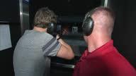 Interior shots of man selecting zombie shooting range target and then firing shotgun at it including reloading of shotgun cartridges via pump hand...