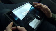 Interior shots of man sitting in taxi using Ipad to browse Sky News Google web pages Man using Ipad in London black cab taxi on December 27 2012 in...