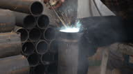 Interior shots of man welding metal tube and using industrial machinery to shape other materials in bomb factory Man welding and using machinery in...