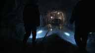Interior shots of miners wearing safety gear being taken in a lift shaft to an underground gold mine miners being briefed and miners chipping pieces...